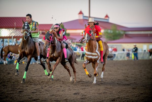 three riders atop horses racing side by side