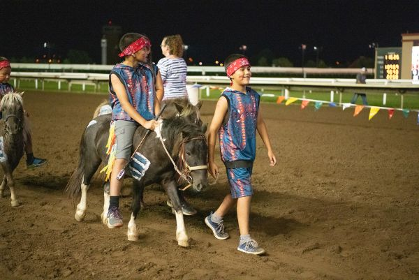 Youth riders presenting ponies before race.