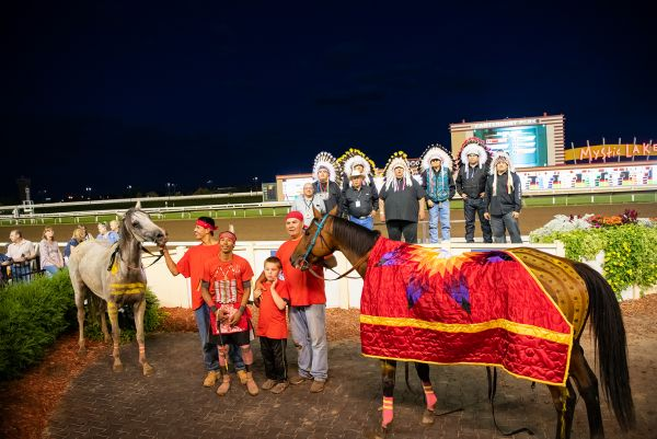 Team presenting horse draped in star quilt in the Winner's Circle